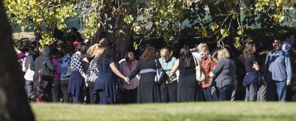 Evacuated workers pray on the San Bernardino Golf Course across the street from a mass shooting at the Inland Regional Center in San Bernardino, Calif., on Wednesday, Dec. 2, 2015. (Gina Ferazzi/Los Angeles Times/TNS) ORG XMIT: 1177505