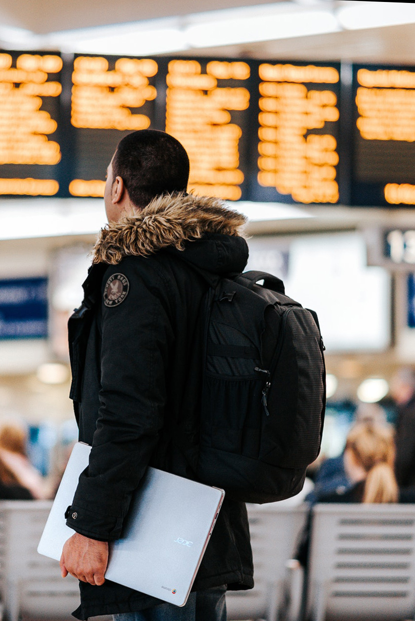 man checking flights at airport while wearing backpack