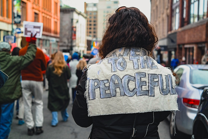 """power to the peaceful"" sign at a protest march"