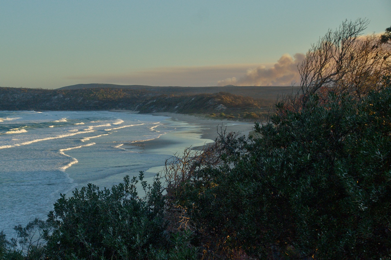 A coastal Australian landscape image depicting large smoke clouds billowing on the horizon.