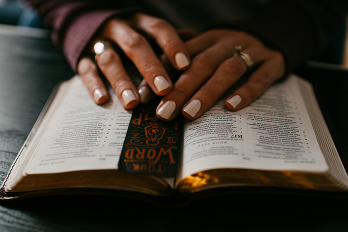 Hands placed over an open bible