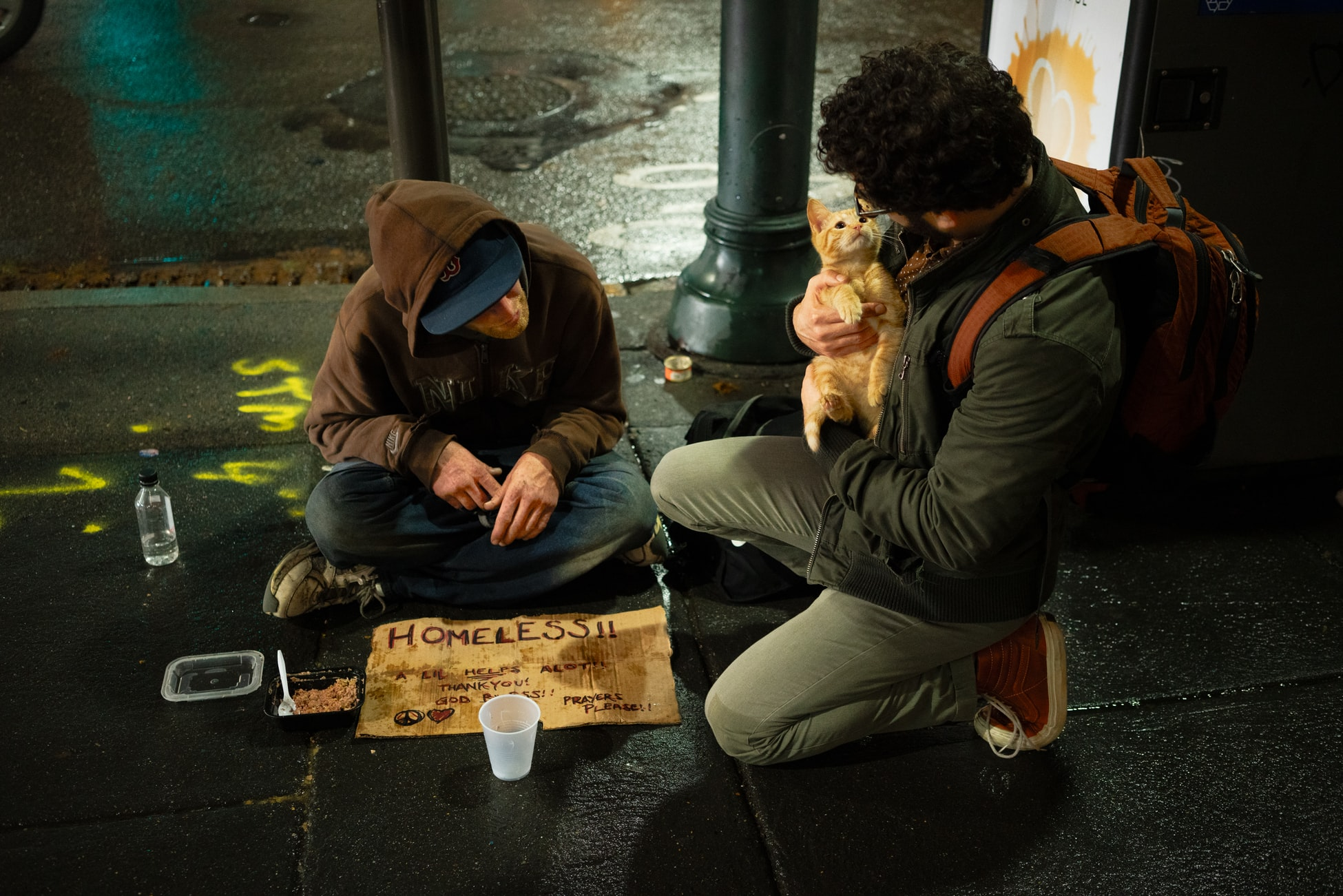 "A photo of a homeless man sitting on the sidewalk with a sign saying ""Homeless! A Little Helps a lot. Thank you, God bless. Prayers please!"" A pedestrian is kneeling beside him petting his kitten and having a conversation with the homeless man."